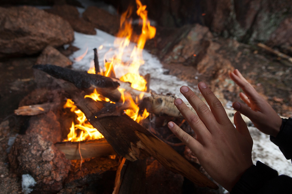 Marco Binotti warms his hands by a fire at his campsite in a cave in McCurdy Park, Lost Creek Wilderness, Colorado.