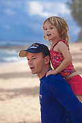 A father with his small daughter on his back on the beach looking excitedly out at the surf in Hawaii