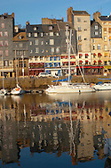 Reflection of harbour buildings and yaughts. Honfleur, Normandy, France. . Honfleur is especially known for its old port, characterised by its houses with slate-covered frontages, painted many times by artists, including in particular Gustave Courbet, Eugène Boudin, Claude Monet and Johan Jongkind, forming the école de Honfleur (Honfleur school) which contributed to the appearance of the Impressionist movement. .<br /> <br /> Visit our FRANCE HISTORIC PLACES PHOTO COLLECTIONS for more photos to download or buy as wall art prints https://funkystock.photoshelter.com/gallery-collection/Pictures-Images-of-France-Photos-of-French-Historic-Landmark-Sites/C0000pDRcOaIqj8E