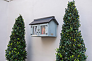A tiny Little Free Library box on the side of a historic home on Lamboll Street in Charleston, SC.