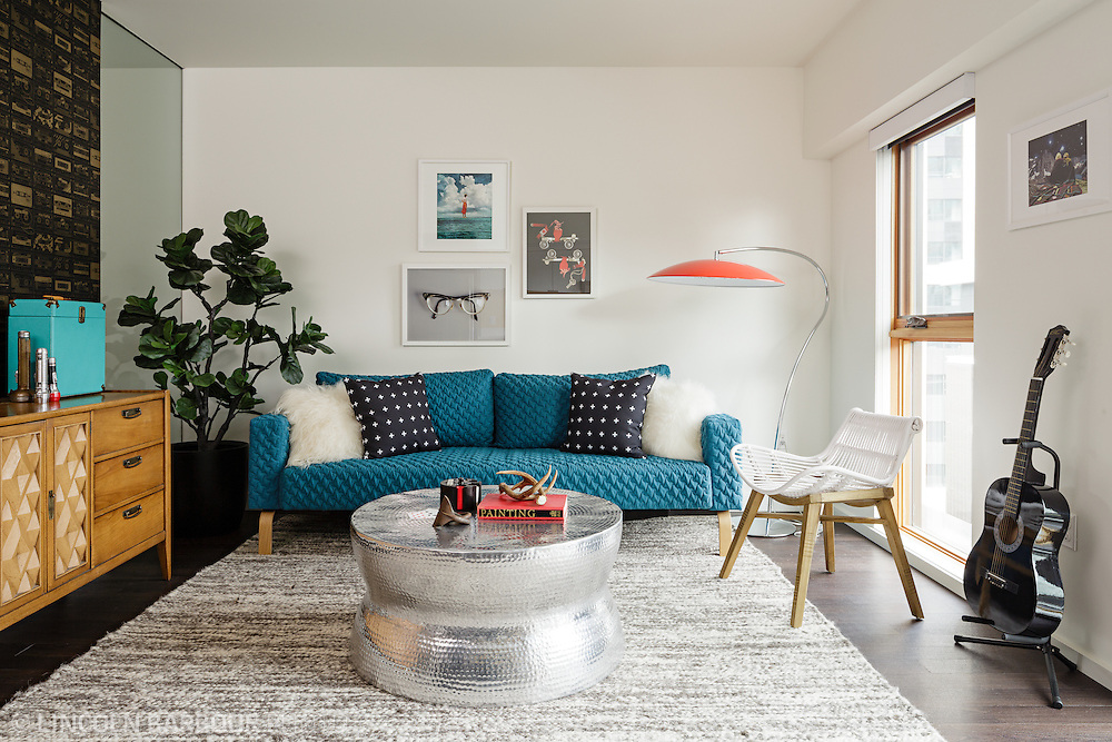 A well decorated apartment living room.  Modern furniture and decor with bright pops of color.