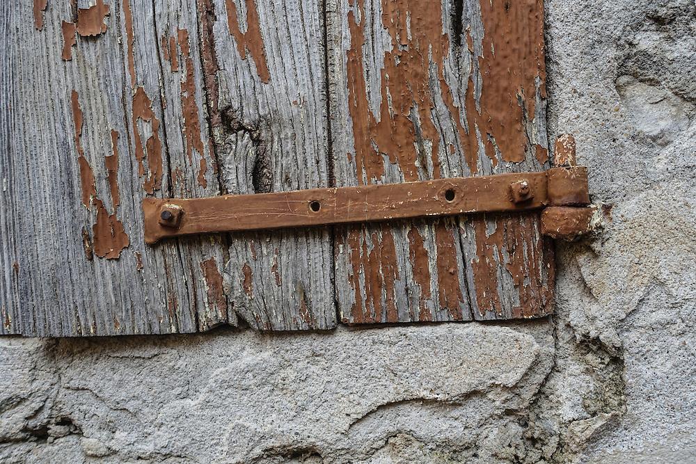 Portion of weathered wooden shutter, with peeling brown paint, is attached to stone wall by long metal hinge painted brown.