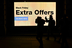 © Licensed to London News Pictures. 23/11/2018. LONDON, UK.  People pass advertising signs on display near Piccadilly Circus on Black Friday.   Traditional retailers face increasing challenges to attract customers against their online competition.  Photo credit: Stephen Chung/LNP