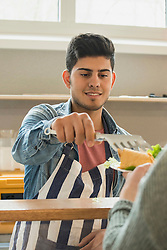 Man serving wrap sandwich to student in canteen School, Bavaria, Germany