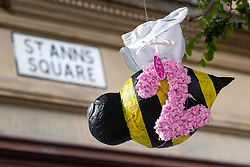"""© Licensed to London News Pictures . 22/05/2019. Manchester, UK . Two bees spelling out """" 22 """" hang from a tree in St Ann's Square . People in St Ann's Square in Manchester City Centre on the second anniversary of the Manchester Arena bombing following a private service in St Ann's Church . On the evening of 22nd May 2017 , Salman Abedi murdered 22 people and seriously injured dozens more , when he exploded a bomb in the foyer of the Manchester Arena as concert-goers were leaving an Ariana Grande gig . Photo credit: Joel Goodman/LNP"""