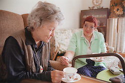 Carer talking with elderly woman,