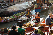 Floating Markets of Southeast Asia<br /> <br /> Floating markets, where goods are sold from boats, are a trademark attraction among the Southeast Asian countries such as Thailand, Indonesia and Vietnam. They originate from a time when water transport played an important role in daily life.<br /> All these countries are located either on islands or on wet lowlands with broad river valleys. Located in tropical climate, this region was thick jungles prior to human development. The first places to be settled were adjacent to the rivers, and the people living there used boats as their main mode of travel rather than trying to push their way through the dense jungle. Although the region is now developed and there is a network of roads connecting all cities and towns, boats are still used for transport and trade by the communities along the waterways, especially by farmers whose farmlands are located by the riverside.<br /> <br /> Farmers bring their produces in boats to the markets and sell them to local dealers directly from the boats, eliminating the need to setup shops in the docks. That way they could quickly sell their products and return back to their home. The local dealers buy the products and sell them to shops in the neighboring towns and to wholesale dealers from the big towns. Floating markets are also a big tourist draw.<br /> The most famous floating market, and a tourist haven, is the one in Damnoen Saduak about 100km southwest of Bangkok. The floating market is crowded with hundreds of vendors and purchasers floating in their small boats selling and buying agricultural products and local food. The market opens in the early morning and closes about an hour before noon.<br /> Amphawa floating market, located in Amphawa district, about 72 km from Bangkok, is not as large as Damnoen Saduak floating market but it is more authentic, with visitors almost exclusively Thais. It is an evening floating market but some stalls are opened at noon too. Other floating markets around Bangkok include Wat Sai Floati