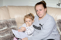 Dionne Burrows, 28, and daughter Ava Apps read a letter from their Quayside House apartment block management, Sanctuary Housing, reminding residents that pest controllers will be arriving to fumigate the residential block following an infestation of false widow spiders. Dionne was bitten on the leg several weeks prior after which her GP prescribed antibiotics. Canning Town, London, October 30 2018.