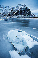 Rock breaks through ice on frozen lake Nedre Heimdalsvatnet, Eggum, Lofoten Islands, Norway