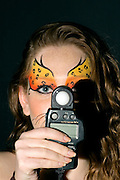 young teenage female model with elaborate tiger make up mask on black background holding up a light meter for the photographer model released studio shot