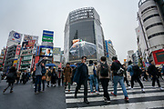 Japanese people and tourists cross the famous Shibuya Scramble crossing in rainy weatherShibuya, Tokyo, Japan. Thursday, November 28th 2019