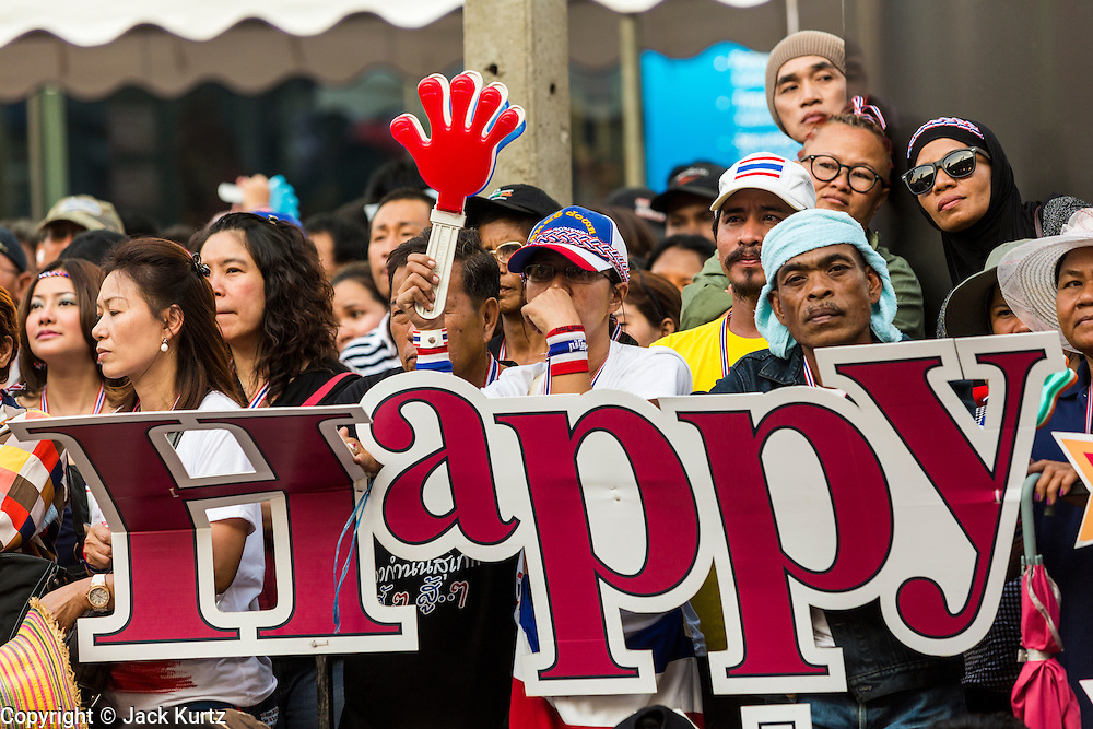 """13 JANUARY 2014 - BANGKOK, THAILAND:  Anti-government protestors behind an old Happy New Year sign in the Asok intersection in Bangkok. Tens of thousands of Thai anti-government protestors took to the streets of Bangkok Monday to shut down the Thai capitol. The protest was called """"Shutdown Bangkok"""" and is expected to last at least a week. The Shutdown Bangkok protest is a continuation of protests that started in early November. There have been shootings almost every night at different protests sites around Bangkok, including two Sunday night, but the protests Monday were peaceful. The malls in Bangkok stayed open Monday but many other businesses closed for the day and mass transit was swamped with both protestors and people who had to use mass transit because the roads were blocked.   PHOTO BY JACK KURTZ"""