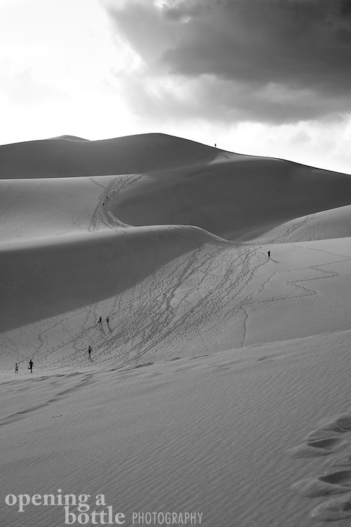 Hikers climb the Great Sand Dunes, Great Sand Dunes National Park, Colorado. Full color image also available upon request.