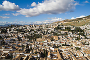 Expansive view from La Alhambra of the whitewashed buildings and tile roofs of Granada, Andalusia, Spain.