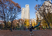 A mother carries a baby through a playground in Shinjuku Chuo park with the towers of the Tokyo Metropolitan Government Building behind, Shinjuku, Tokyo, Japan. Thursday December 12th 2019