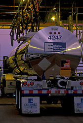 Large liquid transport truck refueling for a delivery at dusk