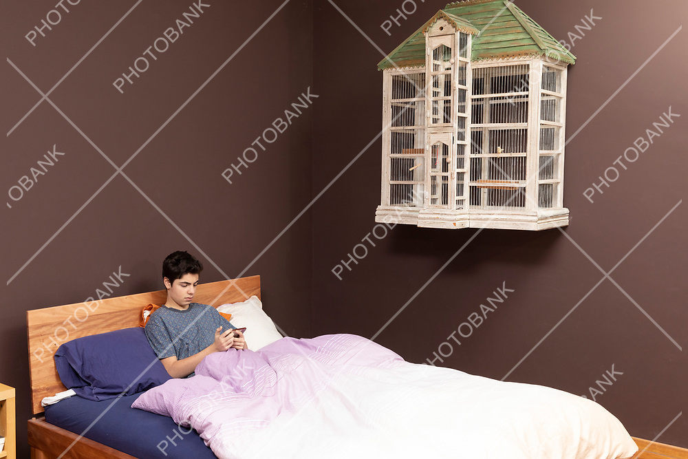 Boy in bed with phone and hanging on the wall a grade empty bird cage