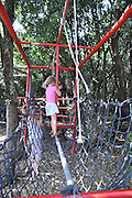 Children's holiday activity Children's adventure and playground child walks across a rope bridge