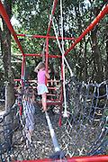 Children's holiday activity Children's adventure and playground child walks across a rope bridge
