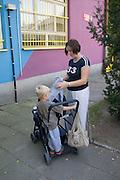 Mom ages 28 and 3 packing stroller outside Rainbow Preschool Teczowe Przedszkole Balucki District Lodz Central Poland