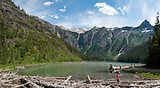 """Hike 4 miles round trip (560 feet gain) to Avalanche Lake in Glacier National Park, Montana, USA. Since 1932, Canada and USA have shared Waterton-Glacier International Peace Park, which UNESCO declared a World Heritage Site (1995) containing two Biosphere Reserves (1976). Rocks in the park are primarily sedimentary layers deposited in shallow seas over 1.6 billion to 800 million years ago. During the tectonic formation of the Rocky Mountains 170 million years ago, the Lewis Overthrust displaced these old rocks over newer Cretaceous age rocks. Glaciers carved spectacular U-shaped valleys and pyramidal peaks as recently as the Last Glacial Maximum (the last """"Ice Age"""" 25,000 to 13,000 years ago). Of the 150 glaciers existing in the mid 1800s, only 25 active glaciers remain in the park as of 2010, and all may disappear as soon as 2020, say climate scientists.(Panorama stitched from 6 overlapping images.)"""