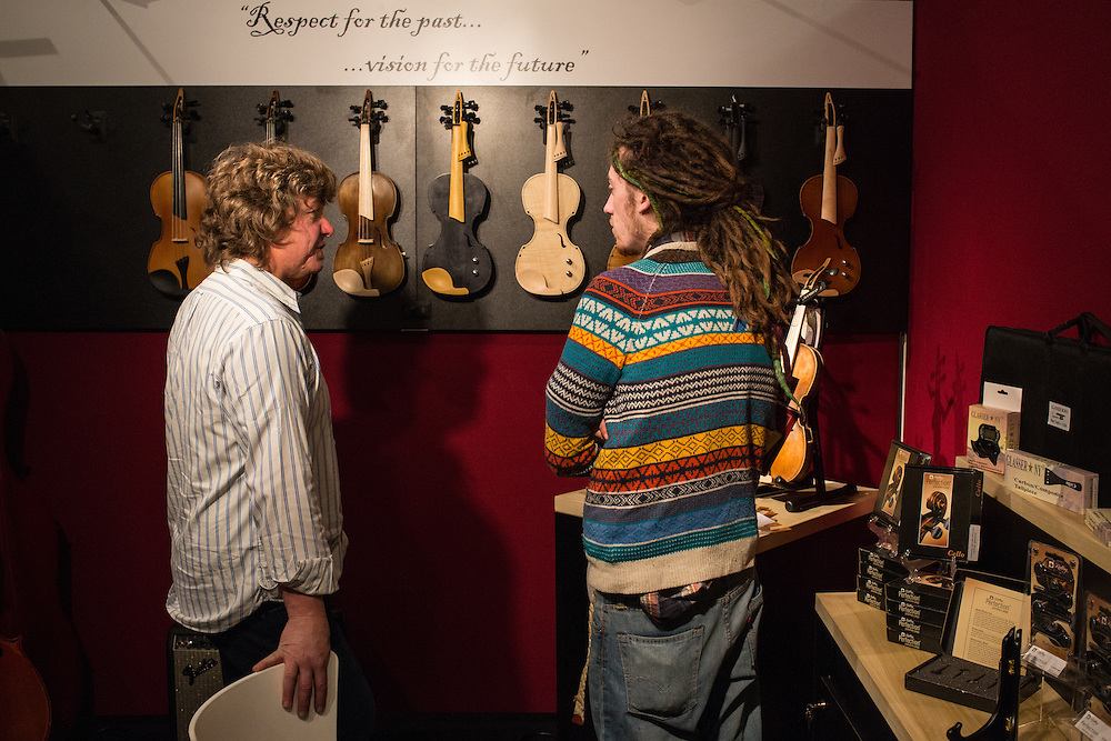 Violin maker Paul Davies, left, of Spur Violins in New York, discusses his new line of electric violins.