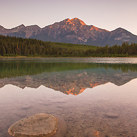 A touch of gold appears on Pyramid Mountain as a new day begins in Jasper National Park, Canada.