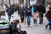 Buskeroutside Oxford Circus as the national lockdown ends and the new three tier system of local coronavirus restrictions begins, shoppers head out to Oxford Street to catch up on shopping as non-essential shops are allowed to reopen on 2nd December 2020 in London, United Kingdom. Many shoppers wear face masks outside on the street as a precaution as there are so many people around.