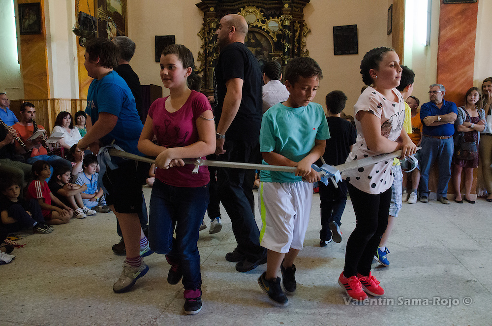 Kids dacing holding wooden swords decorated with blue ribbons during the rehearsal of Cetina's Dance in 'San Juan Lorenzo' hermitage.