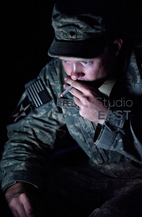 US Army PFC Pelkey smokes a cigarette as he monitors a Puma UAV (Unmanned Aerial Vehicle) on reconnoiter flight over the Pech Valley looking for Taliban fire positions in Nangalam, Kunar Province, eastern Afghanistan. 3 October 2009. UAVs are used extensively in the mountainous region of eastern Afghanistan and Pakistan in reconnaissance and interdiction roles with measurable success against Taliban targets.
