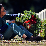 Tess Reusch, of Beaufort, rests against a gravestone as she places a wreath on her husbands grave during the Wreaths Across America Day event at the Beaufort National Cemetery on December 13, 2014. Reusch's husband Monty G. Reusch was a  US Marine Core who passed away in 2000 from pancreatic cancer.  Wreaths Across America day is a day to honor those who gave their lives in service to our country and are buried in national cemeteries across America. Hundreds of sites across the U.S. celebrated Wreaths Across America on Saturday afternoon, Dec 14th, 2013, honoring veterans across the country.