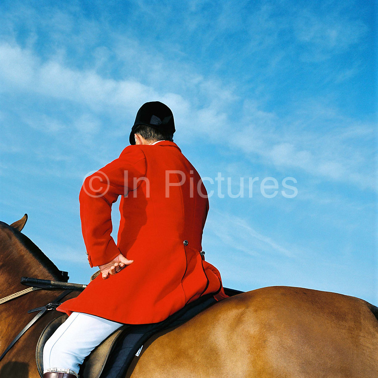 The 'Master of the Hounds' wearing a red coat on horseback, Exmoor, Somerset, UK. Stag hunting is an activity involving the tracking, chase and sometimes killing of a stag by trained hounds and a group of followers lead by a 'master' who follow the hounds on foot or on horseback. This controversial sport, was banned in England and Wales in November 2004.