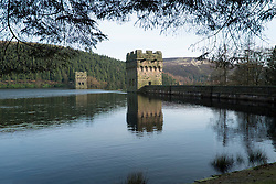 """The View north from the West bank of the Derwent Reservoir in Derbyshire, England is the middle of three reservoirs in the Upper Derwent Valley, the higher reservoir being Howden to the North and the lower being Ladybower to the south. Between them they provide practically all of Derbyshire's water, as well as to a large part of South Yorkshire and as far afield as Nottingham and Leicester.<br /> Begun in 1902 this neo-Gothic solid masonry dam wall is built from huge stones that were transported along a specially created railway from the quarries at Grindleford. Over 1,000 workers lived in a specially constructed and self-contained town of Birchinlee also known as """"Tin Town"""". Derwent reservoir began being filled in November 1914, and overflowed for the first time in January of 1916. Covering an area of 70.8 hectares (175 acres) and at its deepest point is 34.7 metres (114 ft) the dam can support a total of 9.64 million cubic metres of water.<br /> For 6 weeks during the Second World War the reservoir was used by the pilots of the 617 Squadron """"the Dambusters"""" to practice their low-level flying skills needed for Operation Chastise, because of the Derwents similarity to the operations German target. In for 2 weeks in 1954 the the sound of Lancaster bomber engines could be heard again over the Derwent as the reservoir stood in for the German dams a second time. This time for the filming of the """"The Dambusters"""" starring Richard Todd as Guy Gibson. The west tower of the dam wall is home to Derwent Valley Museum and includes a permanent memorial to 617 Squadron to which is visible even when the Museum is closed. <br /> <br /> 22  March 2015 Image © Paul David Drabble www.pauldaviddrabble.co.uk"""