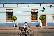 A man rides a bicycle past a colorful colonial building in Actopan, Hidalgo, Mexico.