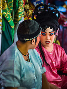 17 FEBRUARY 2016 - BANGKOK, THAILAND: Women in a small opera troupe chat while putting on their makeup before a performance in Bangkok. The small troupe travels from Chinese shrine to Chinese shrine performing for a few nights before going to another shrine. They spend about half the year touring in Thailand and the other half of the year touring in Malaysia. Members of the troupe are paid about 5,000 Thai Baht per month (about $140 US). Chinese opera was once very popular in Thailand, where it is called Ngiew. It is usually performed in the Teochew language. Millions of Chinese emigrated to Thailand (then Siam) in the 18th and 19th centuries and brought their culture with them. Recently the popularity of ngiew has faded as people turn to performances of opera on DVD or movies. There are still as many 30 Chinese opera troupes left in Bangkok and its environs. They are especially busy during Chinese New Year and Chinese holiday when they travel from Chinese temple to Chinese temple performing on stages they put up in streets near the temple, sometimes sleeping on hammocks they sling under their stage. Most of the Chinese operas from Bangkok travel to Malaysia for Ghost Month, leaving just a few to perform in Bangkok.     PHOTO BY JACK KURTZ