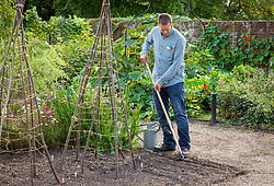 Sowing hardy annuals in drills in a border outside. Making drills with a hoe.
