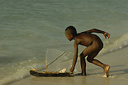 Vezo (Fishing people) children playing on the beach with their model pirogues. Vezo are also known as Vezo-Sakalava as they are not generally recognised as a separate tribe but a clan of the Sakalava. They live on the coast in the region of Morondava in the west to Faux Cap in the south. They are mainly fishermen. They are also known for their tombs, which are graves dug into the ground surrounded by wooden palisages, the main posts of which are crowned by erotic wooden carved figures.<br />