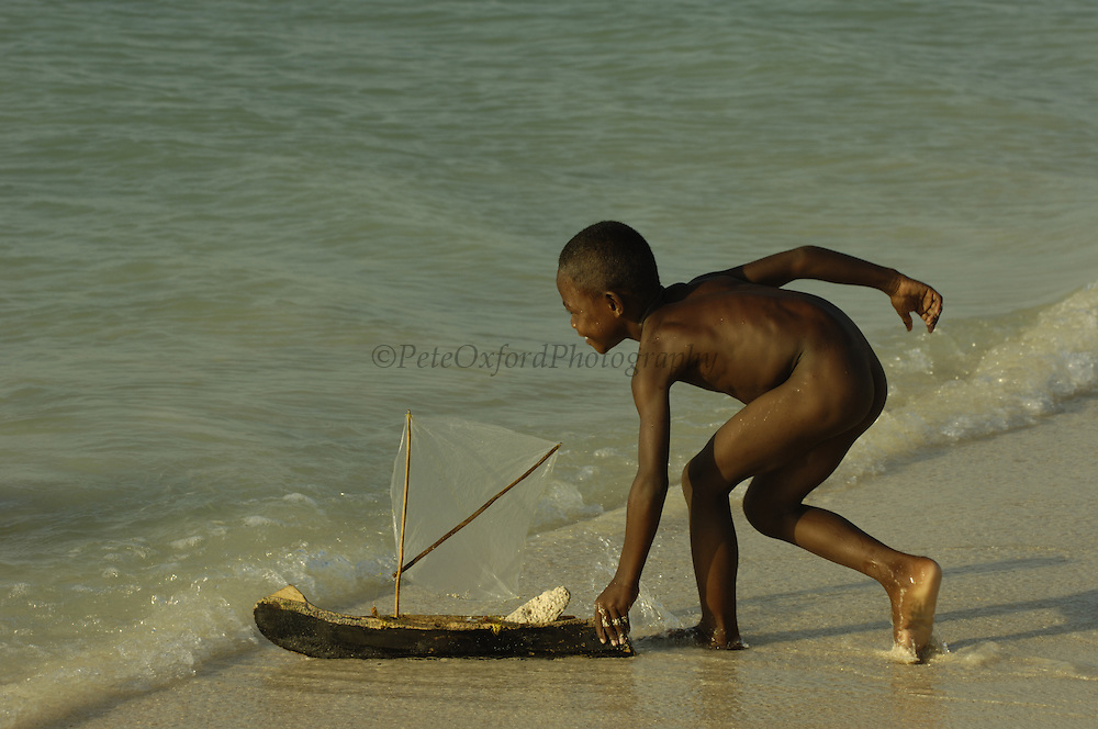 Vezo (Fishing people) children playing on the beach with their model pirogues. Vezo are also known as Vezo-Sakalava as they are not generally recognised as a separate tribe but a clan of the Sakalava. They live on the coast in the region of Morondava in the west to Faux Cap in the south. They are mainly fishermen. They are also known for their tombs, which are graves dug into the ground surrounded by wooden palisages, the main posts of which are crowned by erotic wooden carved figures.<br />Beheloka Vezo fishing village.  South-western MADAGASCAR