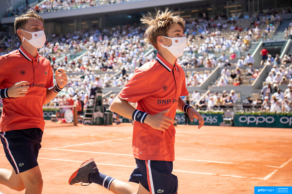PARIS, FRANCE June 13. Ball boys and ball girls change shifts during the Novak Djokovic of Serbia match against Stefanos Tsitsipas of Greece on Court Philippe-Chatrier during the Men's Singles Final at the 2021 French Open Tennis Tournament at Roland Garros on June 13th 2021 in Paris, France. (Photo by Tim Clayton/Corbis via Getty Images)