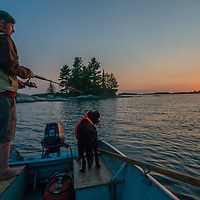 While his dog watches, a fisherman casts into Lake of the Woods, Ontario, Canada.