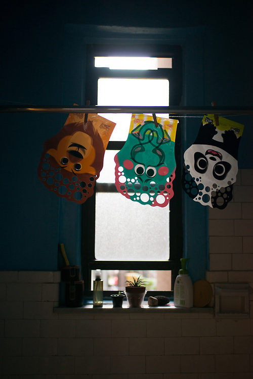 """Three """"bubble making gloves"""" drying in our bathroom, backlit by late afternoon sun."""