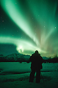 Alaska. Aurora borealis or northern lights. A photographer shoots the aurora near Palmer.