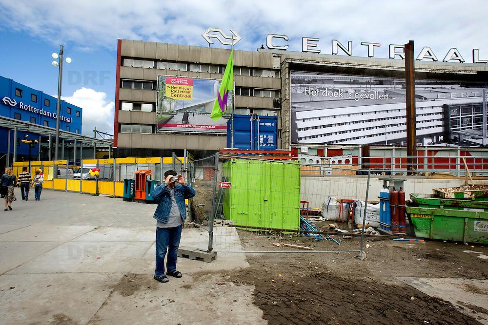 """Nederland Rotterdam 3 september 2007 20070903 .Voorbijganger/ man fotografeert de enorme bouwput voor het voormalige centraal station. Op de achtergrond op de gevel van het voormalige centraal station hangt het doek """" Het doek is gevallen """" Binnenkort zal het pand het definitief gesloopt worden.  ."""" Het doek is gevallen """" Zondag 2 september is het doek letterlijk doek gevallen voor het in 1957 geopende gebouw. Over enkele weken wordt de schepping van architect Sybold van Ravesteyn gesloopt en komt op het Stationsplein een nieuwe OV-terminal, die na 2011 ruim 300.000 reizigers per dag moet kunnen verwerken. Voorbijgangers maken een foto van het oude bekende centraal station, dat sinds 1957 dienst heeft gedaan. Een gloednieuw station zal op deze plek verrijzen. Op de achetrgrond links het tijdelijke centraal station. ..Het tijdelijke station dat de periode overbrugt tussen de sloop van het oude Rotterdam CS en de bouw van een nieuw station, kost 12 miljoen euro. Dat is een schijntje vergeleken met het half miljard waarop het nieuwe is begroot. De bedoeling is dat de tijdelijke bebouwing in februari klaar is. Het blijft open tot 2010. Het oude gebouw maakt plaats voor vijf tijdelijke. Daarvan zijn er vier voor de reizigers en een voor het personeel van de Spoorwegpolitie. ..Tijdelijk Rotterdam Centraal.1 september 2007..Alle treinreizigers opgelet! Vanaf 2 september sta je voor een dichte deur als je bij Rotterdam Centraal op de trein wilt stappen. Tenzij je de ingang van het tijdelijke Rotterdam Centraal al gevonden hebt. ..Naast het oude vertrouwde station staat al een tijdje een groot blauw gebouw en vanaf 2 september kun je daar op je trein stappen. Je kunt er zelfs een kopje koffie halen, of kleine boodschappen doen. Alle winkels zijn namelijk gewoon verplaatst naar het grootste tijdelijke station van Nederland...Het Centraal Station was al een hele tijd een grote bouwput, want er wordt heel hard gewerkt aan een nieuw, beter en vooral moderner station. Maar omdat"""
