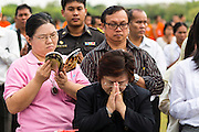 "23 APRIL 2013 - BANGKOK, THAILAND:   A Thai woman reads while everyone around her prays during the opening ceremony to mark Bangkok as the World Book Capital City 2013. UNESCO awarded Bangkok the title. Bangkok is the 13th city to assume the title of ""World Book Capital"", taking over from Yerevan, Armenia. Bangkok Governor Suhumbhand Paribatra announced plans that the Bangkok Metropolitan Administration (BMA) intends to encourage reading among Thais. The BMA runs 37 public libraries in the city and has modernised 14 of them. It plans to build 10 more public libraries every year. Port Harcourt, Nigeria will be the next World Book Capital in 2014..PHOTO BY JACK KURTZ"