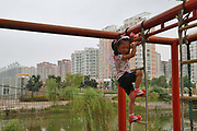 A young girl climbs the jungle gym at a small amusement park in the new district of Yangzhou, Jiangsu Province, China on 19 July 2012. While the Chinese government has tried various ways to cool down the property market, real estate prices have still seen a steady increase in recent years, proving hard for the country to move away from an investment driven economy.