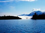 Cessna 206 on floats landing in channel of Hardenburg Bay with fog over Lake Clark, Port Alsworth, Lake Clark National Park and Preserve, Alaska.