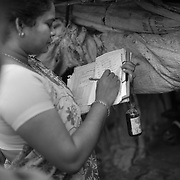 Vaccinator documenting details of Basas (temporary settlement) on the revers of the house-to-house tally sheet during the vaccination day on one of the flooded Kosi riverine area near Kusheshwar Astan East, Bihar.