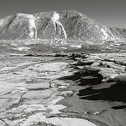 """Sand blown down Taylor Valley ends up on the sea ice. The snow figures on Mt. Coleman are know locally as """"two peeing men"""". A comforting landmark I can see from Observation Hill 50 miles away at McMurdo Station."""
