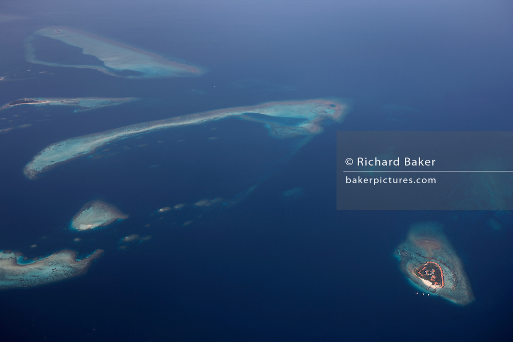 An aerial view of unidentified islands seen from a regional aircraft passing overhead the atolls and islands to the north Malé, capital of the Indian Ocean Republic of the Maldives. We see the perfectly clear blue sea surrounding the islands and tiny sandbanks of white coral beach sand, all of which are in jeopardy of rising sea levels as global warming makes sea level locations like this vulnerable to being overwhelmed. The only sign of life is the tiny island in the bottom right of frame where holiday resort accommodation ring this dot in the ocean. The Maldives comprise of twenty-six atolls, featuring 1,192 coral islands of which 80 are holiday resorts with 200 inhabited by indigenous communities. This Islamic nation of 298 sq km (115 sq miles), lie seven hundred kilometres (435 miles) south-west of Sri Lanka..