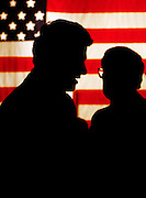 A silhouetted President Bill Clinton (left) talks with US Senator Sam Nunn (D-GA). Nunn is chairman of the powerful senate Armed Services Committee. A large American flag hangs in the background.